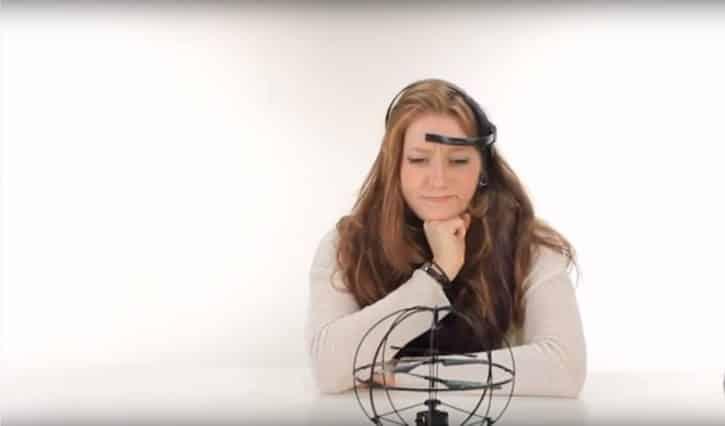 Une femme se concentre pour actionner le drone.