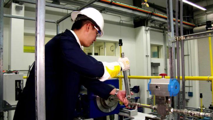 Un ouvrier utilise le RoboGlove pour travailler avec un outil.