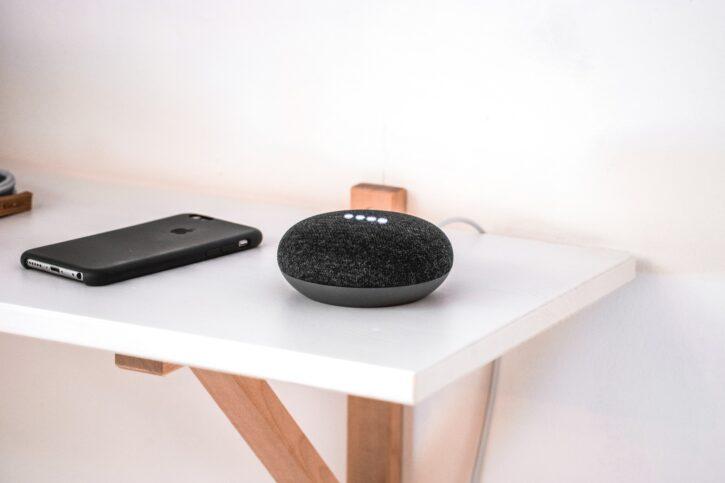 Google Home Mini posé à coté d'un iPhone