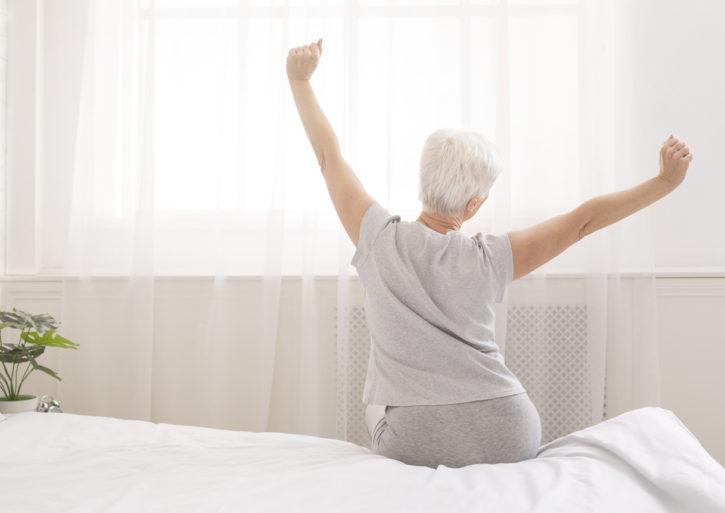 Femme senior au réveil dans une chambre avec des objets connectés
