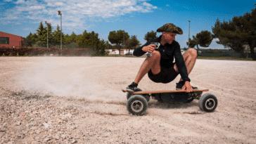 Homme qui fait su skate électrique sur de la terre